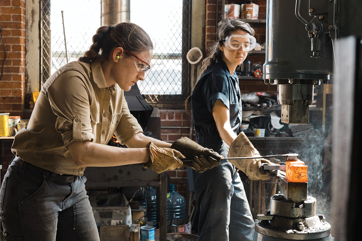 Alaina Mahoney, left, of Providence-based A.M. Design & Fabrication LLC, works with assistant Erica Compton heating metal in a forge to hammer out a mirror frame for Mahoney's upcoming product line release. / COURTESY RUE SAKAYAMA PHOTOGRAPHY