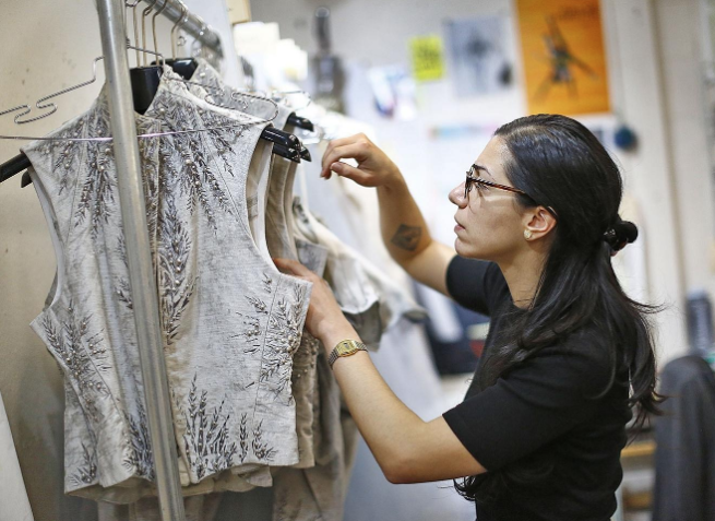 """Boston Ballet draper, Sara Kirk of Quincy, organizes a rack of """"Nutcracker"""" costumes weeks before opening night - photo by Greg Derr of The Patriot Ledger"""