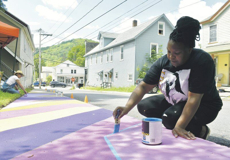 Destiny Palmer painting a mural in Roxbury