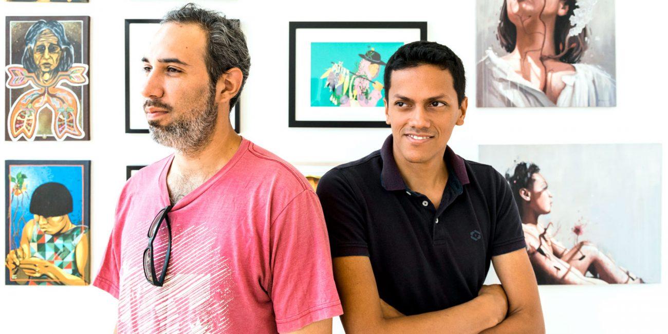 Felipe Ortiz, founder of the Fresco Exchange, left, and Jesus David Rodriguez of Grafica Mestiza stand in the community gallery at GALA, surrounded by art from artists of the Fresco Exchange. (Spenser R. Hasak)