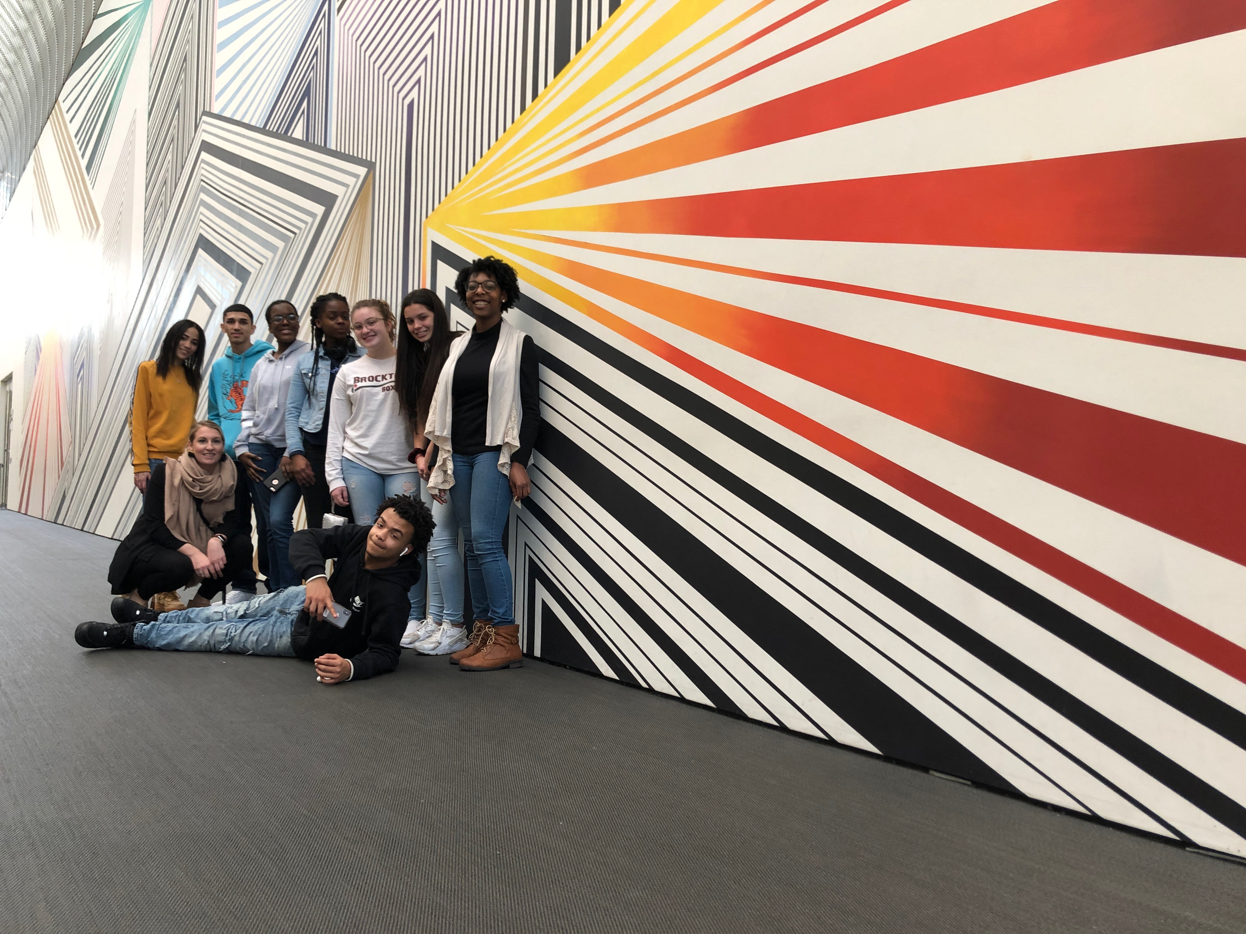 Melanie blood and her high school students in front of her mural