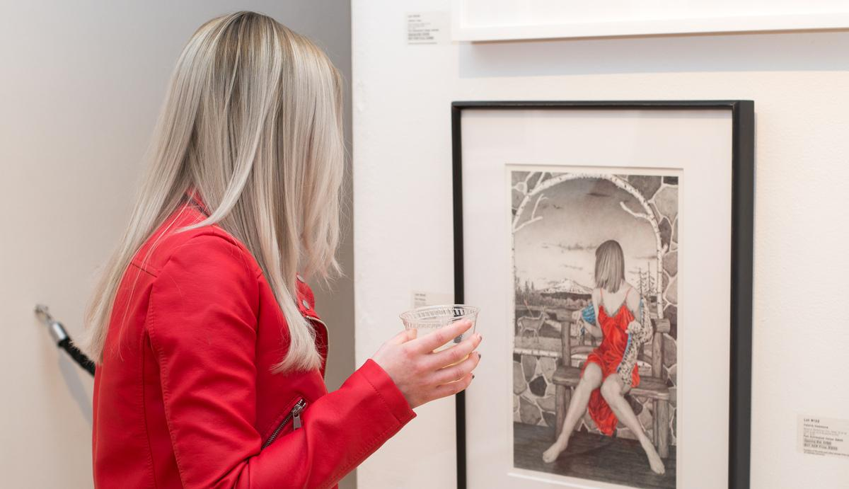 Blonde woman looks at auction artwork from the Auction Preview Party in 2018