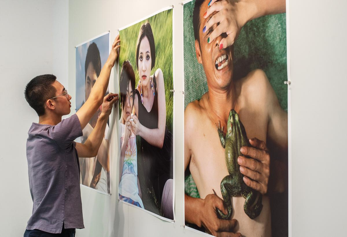 Grad student Zhidong Zhang hanging his artwork