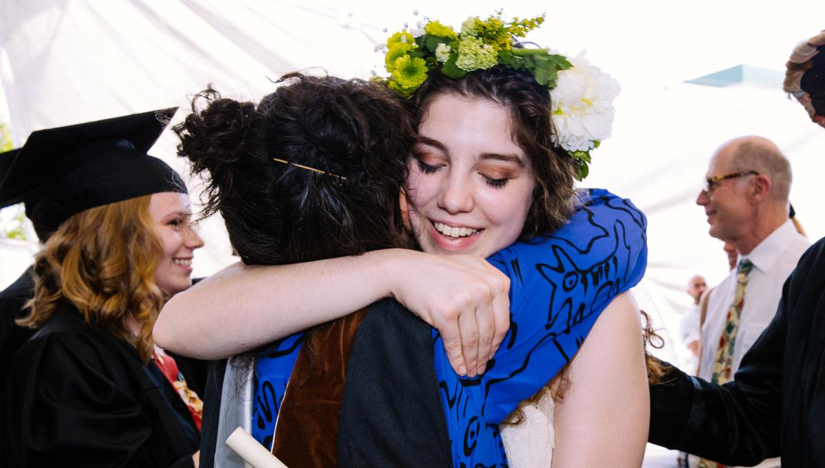 Student in a flower crown hugging a faculty member at the 2019 MassArt Commencement