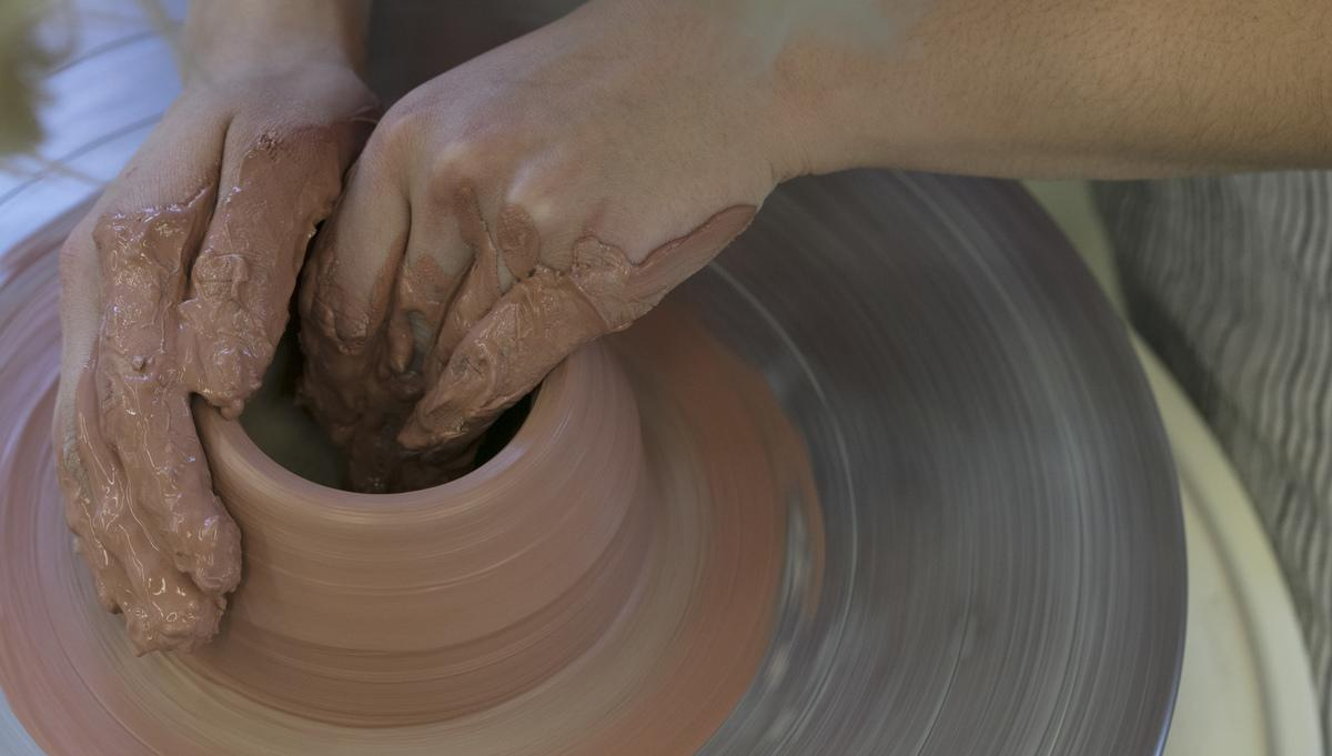 Two hands on the clay working wheel