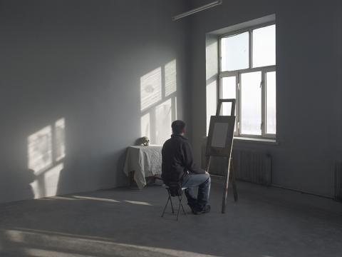 An artist seated an an easel looking at a skull on a desk by Hai Bo