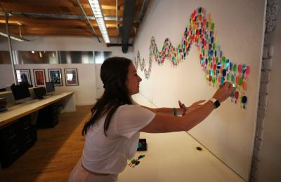 Photo of woman leaning over to add a colored raindrop to Cheryl Sorg's installation