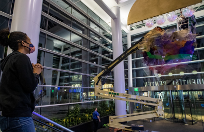 "Artist Cicely Carew watches as globes are suspended from her ""Alta Major"" piece to be installed in the front entrance of the Prudential Center. (Jesse Costa/WBUR)"