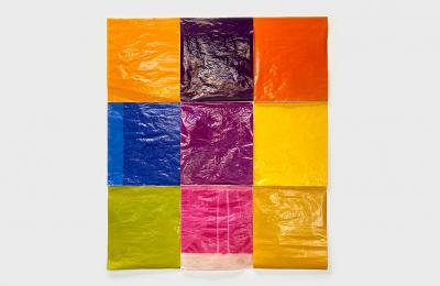 Photo of a 2D piece - 9 rectangles gridded in a 3 by 3 rectangle; each one a different solid color, made of wrapping paper