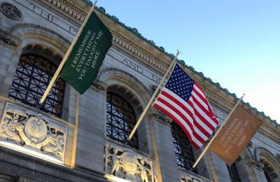 Image of artist flags and the American flag flying in front of the Boston Public Library.